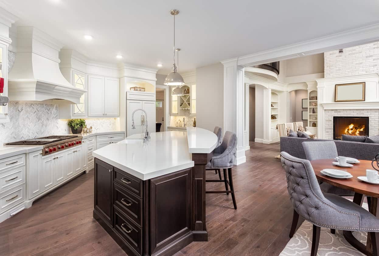 This kitchen features white cabinetry and a white countertop island with a bar stool on the hardwood flooring.