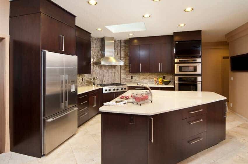 This kitchen with triangular matching island featuring an expanse of the white glossy countertop. The stainless steel appliances match the minimalist dark wood.