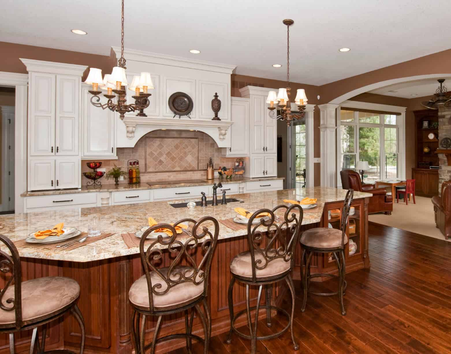Luxury custom design in a large, open kitchen features immense island done in natural wood tones, with built-in glass cabinetry, dining area, and full sink on a marble countertop.