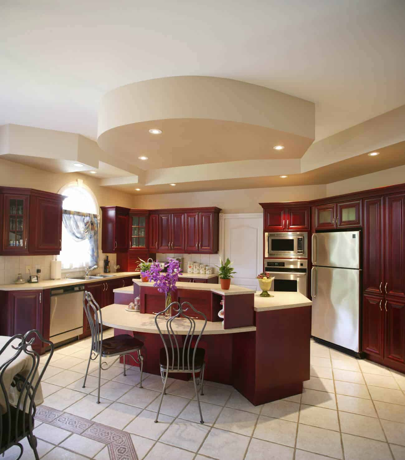 This kitchen features redwood cabinetry and beige tile flooring and countertops. This kitchen lit by recessed ceiling lights.