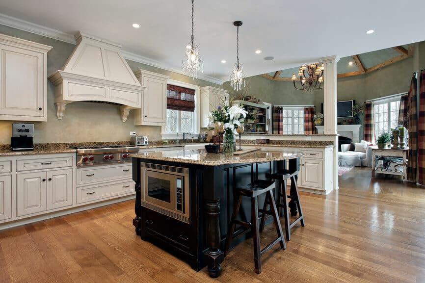 The island stands in sharp contrast, flaunting a black stained wood construction and beige granite countertop.