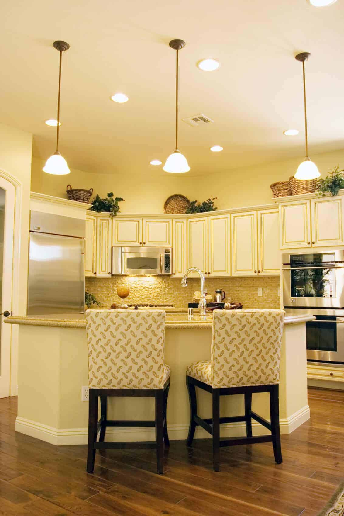 An elegant kitchen features a marble countertop island and stainless steel appliances and this room brighten by recessed ceiling lights and pendant lights.