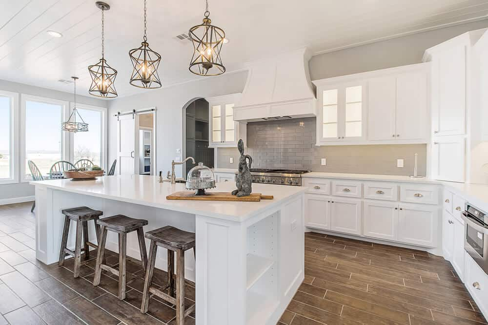 Luxury white kitchen with pendant lighting over the central island, a breakfast area by the windows, and a walk-in pantry.