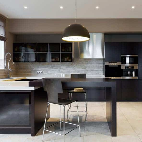 This kitchen features a white countertop and a built-in table with two chairs lightens by pendant lights.