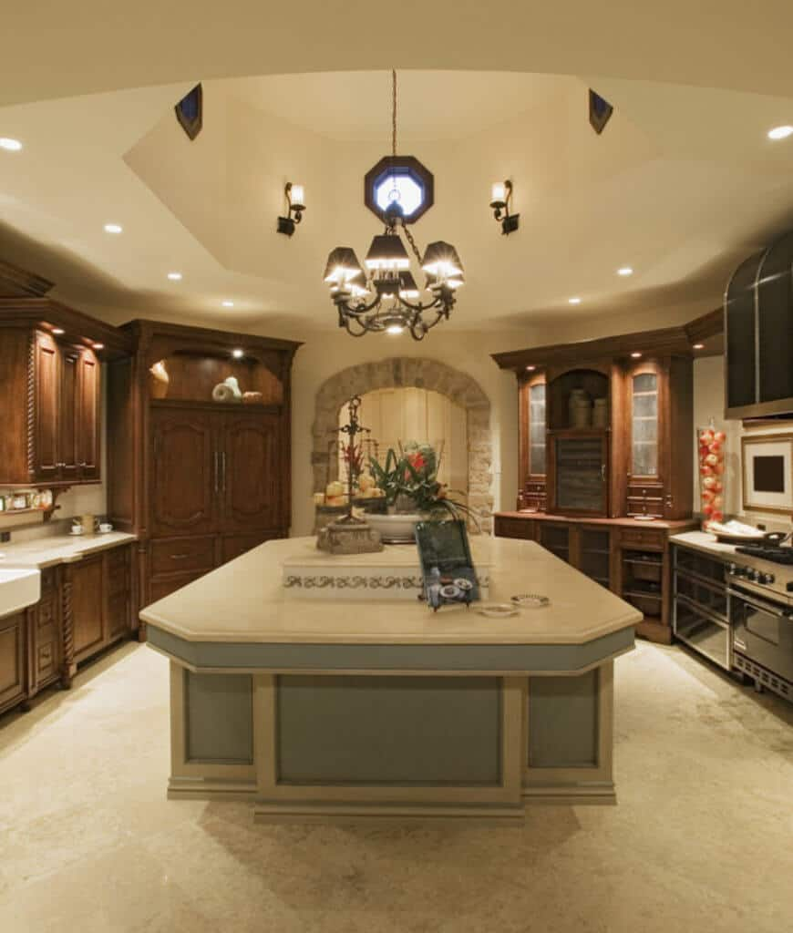 Warm kitchen lighted by a dome pendant chandelier that hung over the kitchen island topped with a beige granite counter