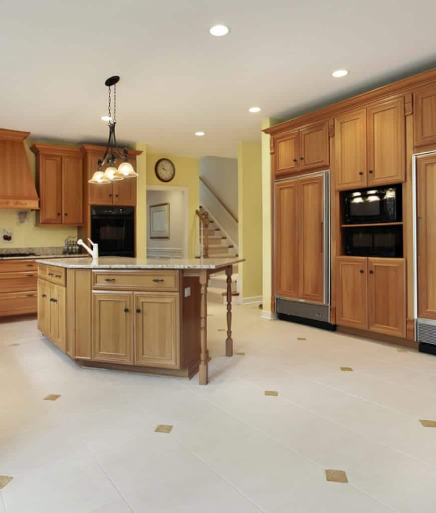 This kitchen highlights wooden cabinetry fitted with black appliances. It has yellow dividers and beige tiled ground surface highlighted with precious stone patterns.
