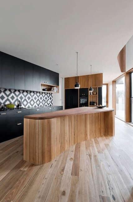 Stylish kitchen flaunts dark cabinetry highlighted with an eye-catching diamond pattern tile backsplash alongside a curved breakfast bar lit by a couple of dark pendants.