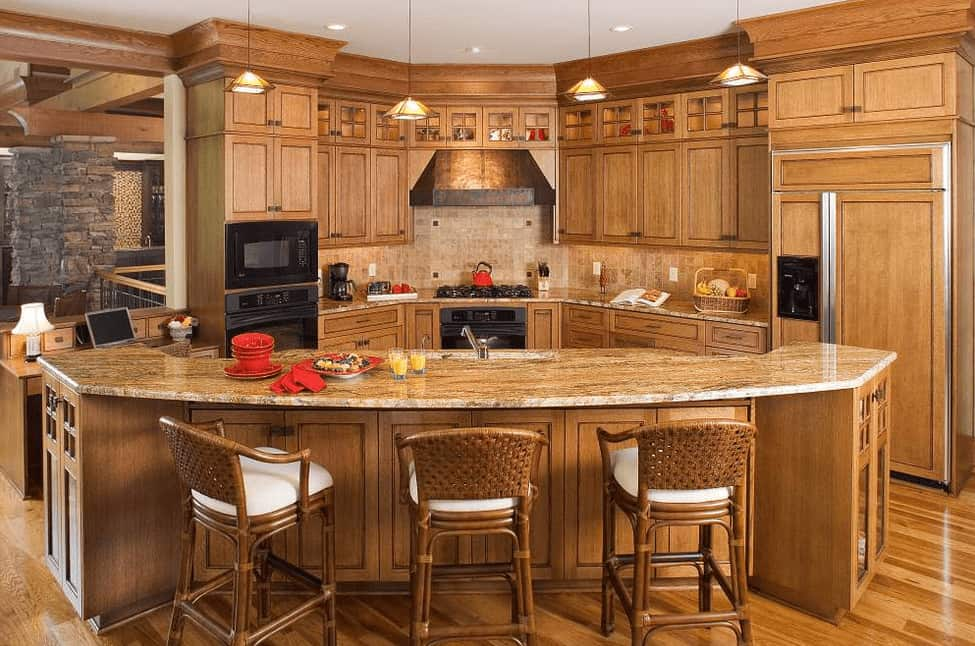 Warm kitchen with a wooden breakfast bar that is fixed with wicker counter seats fitted with white cushions.