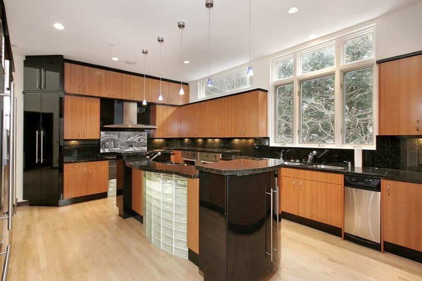This kitchen combines the smooth dark finish of the appliances with corresponding points in the wooden cabinetry.