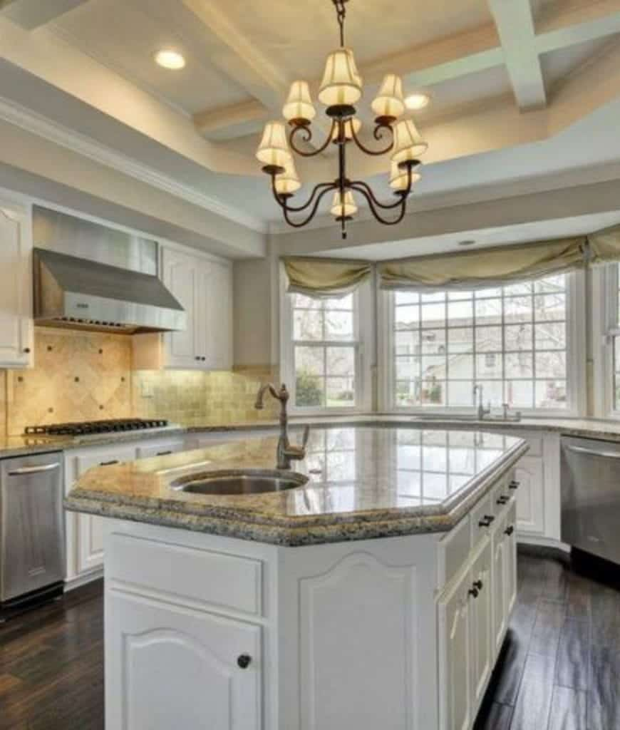 The rustic kitchen offers chandelier and white cabinetry. It includes a gray breakfast island over wood plank flooring.