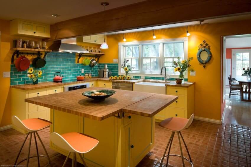 Modern bar stools encompass a wooden top island over terracotta flooring. It is accompanied by stainless steel appliances and yellow cabinetry that is complemented with green metro tile backsplash.