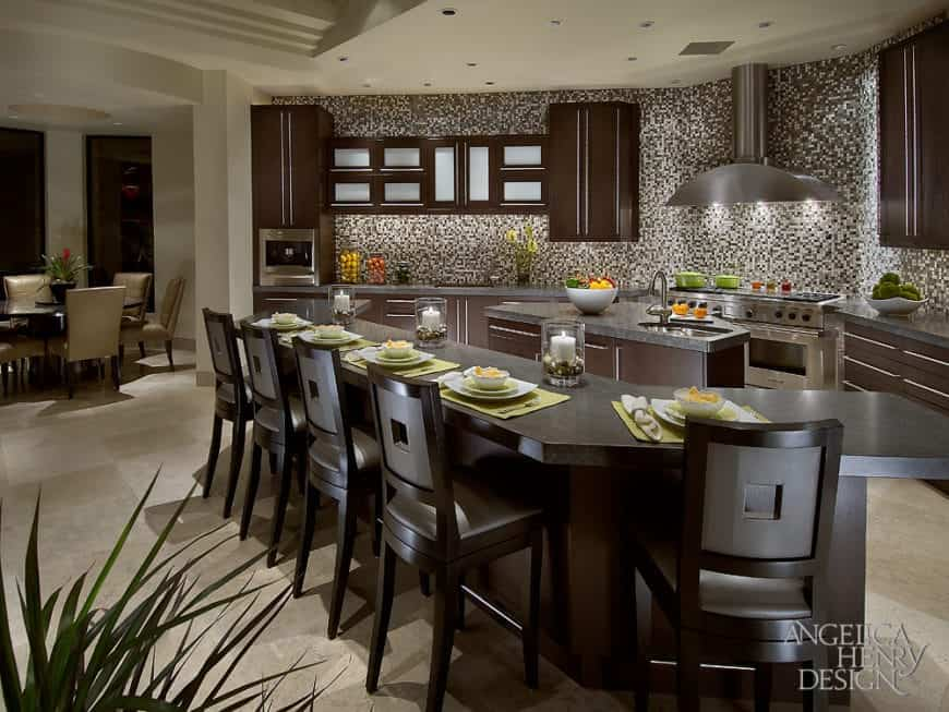 Fabulous kitchen lined with a curved wooden island bar surrounded by cushioned chairs. It has a stainless steel range hood fixed to the glittering mosaic tiles backsplash.