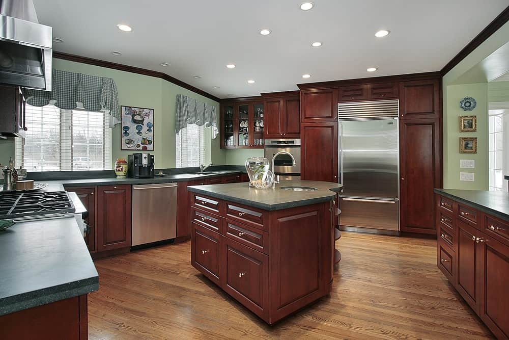 This kitchen features dark wood kitchen cabinets and stainless steel appliances. It also has green walls and a white ceiling with recessed lights.