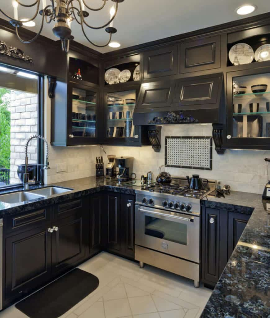U-shaped kitchen with dark and glass-front cabinetry filled with decorative dinnerware. It includes a black countertop fitted with stainless steel extend and double sink with pull down sprayer.