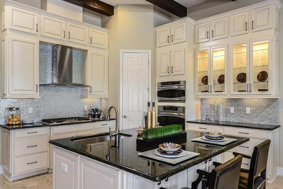 This kitchen offers stylish tiles backsplash and elegant black granite countertops on both kitchen counters and center island.