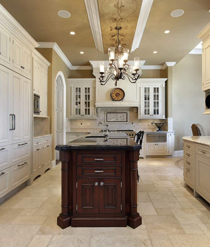 Beige kitchen surrounded with white cabinetry that's contrasted with a dark wood central island bested with dark granite counter and lit by a chandelier.