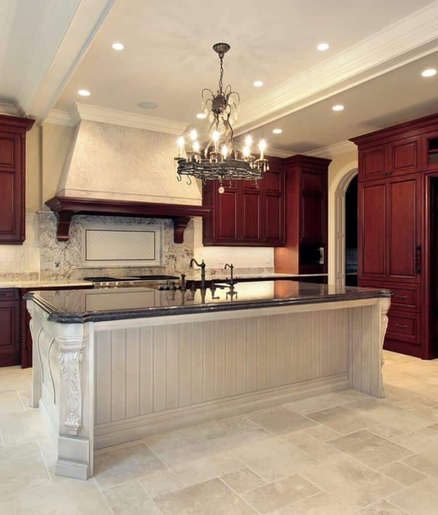 A candle chandelier coordinated with pot rack hangs over the solid island bar bested with a black countertop in this kitchen with rich wood cabinetry and vent hood fixed to the marble backsplash.