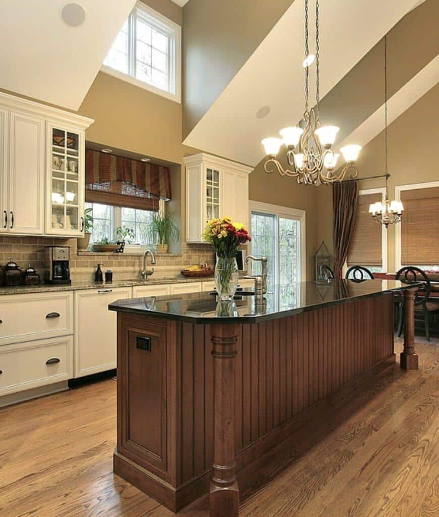 This kitchen exhibits a beadboard central island and dining set by the coated windows secured with wicker roman shades and black countertops.