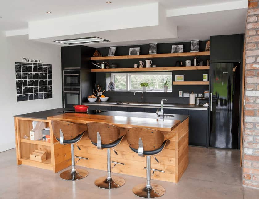 Black appliances hide in the black cabinetry in this industrial kitchen with a wooden island bar supplementing with the floating shelves loaded up with cups and casings.
