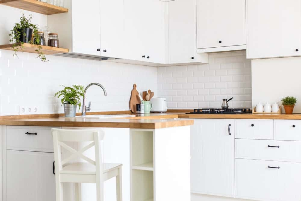 This kitchen feature floating rustic shelves and wooden countertops match the white cabinets and drawers.