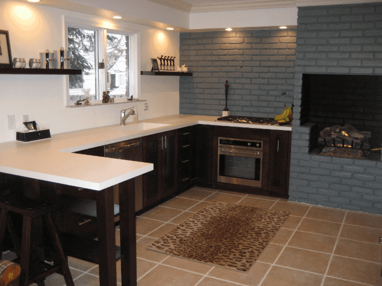 U-shaped kitchen highlights floating shelves and dull wood cabinets bested with white quartz counter. It additionally has an open chimney fixed to the dim brick wall.