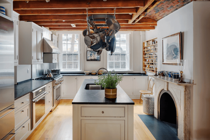 A metal pot rack hangs over a central breakfast island in this kitchen with coordinating white cabinetry and floating shelves.