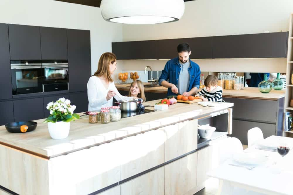 A family helping each other inside the kitchen with a modern design.