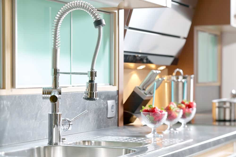 This kitchen's sink is installed with a sprayer faucet perfect for washing dishes and vegetables.