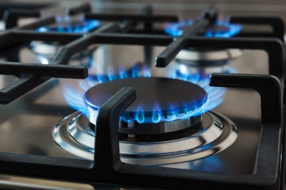 Stainless steel kitchen stove surface with cast-iron grills over the gas burners.