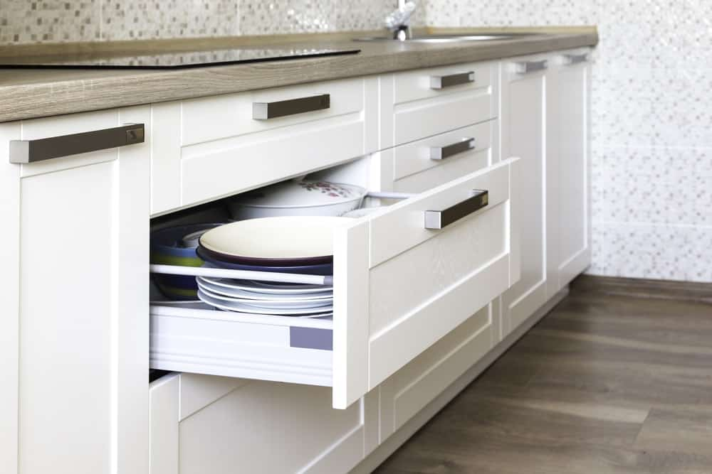 The white shaker drawers of this kitchen's cabinetry is fitted with rollers for easy use.