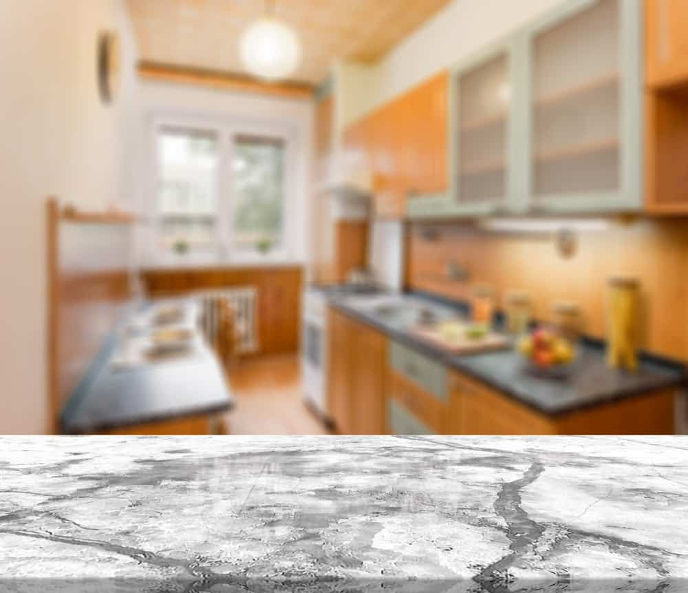 The breakfast bar of this kitchen has a smooth stone countertop.