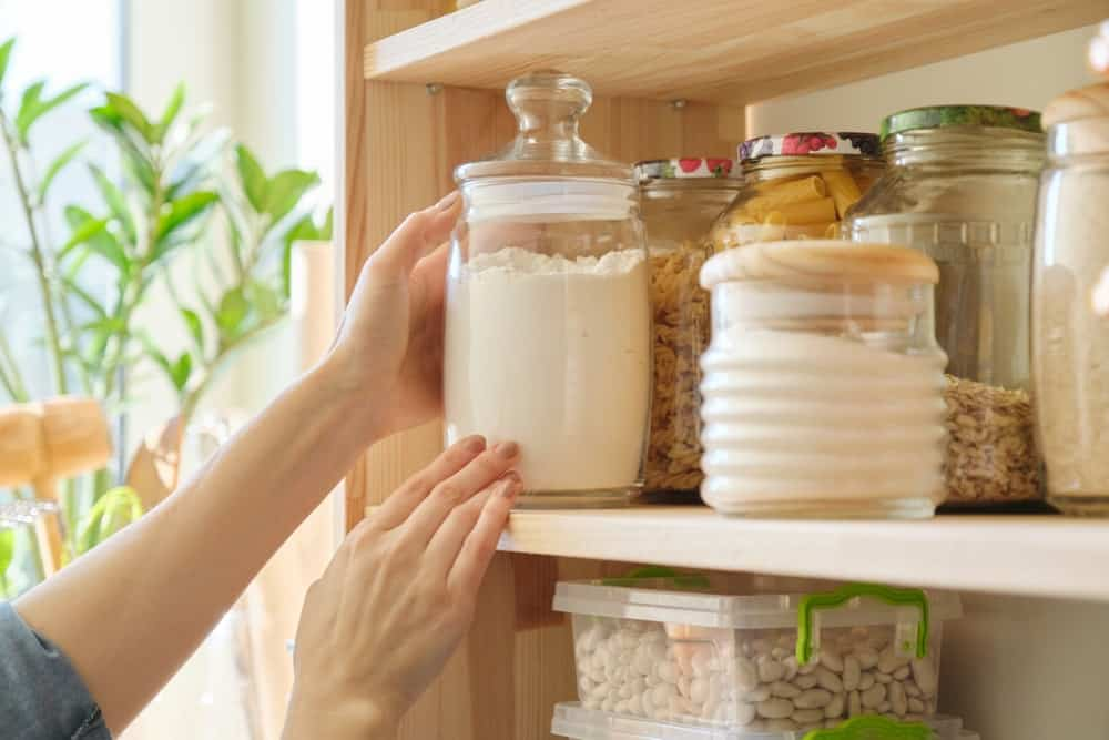 This kitchen's pantry has wooden shelves for storing jars of food.