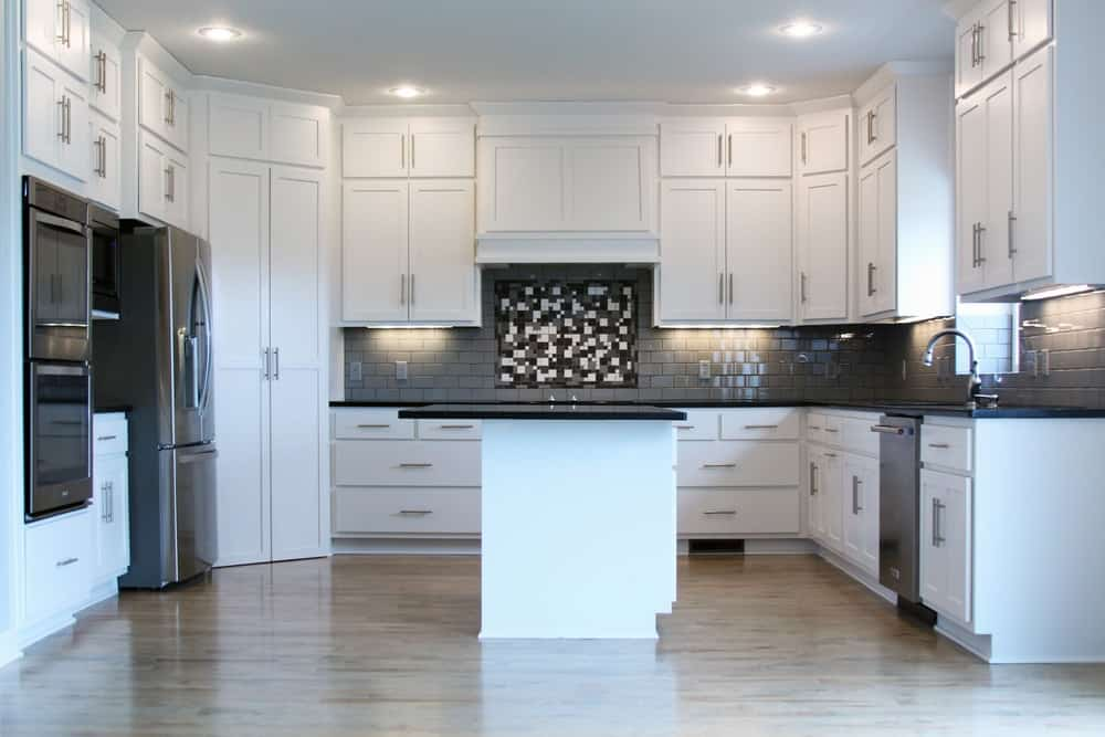The dark gray backsplash of this kitchen is complemented by the lighting underneath the floating cabinets.