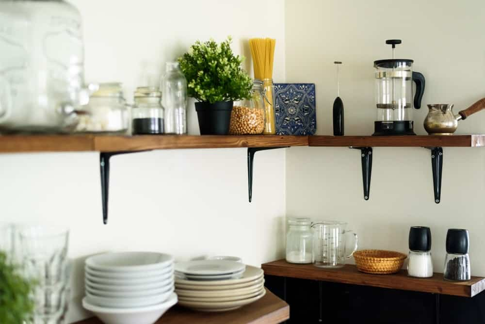 This kitchen's surfaces are filled with various dishware and display leaving room to work with.