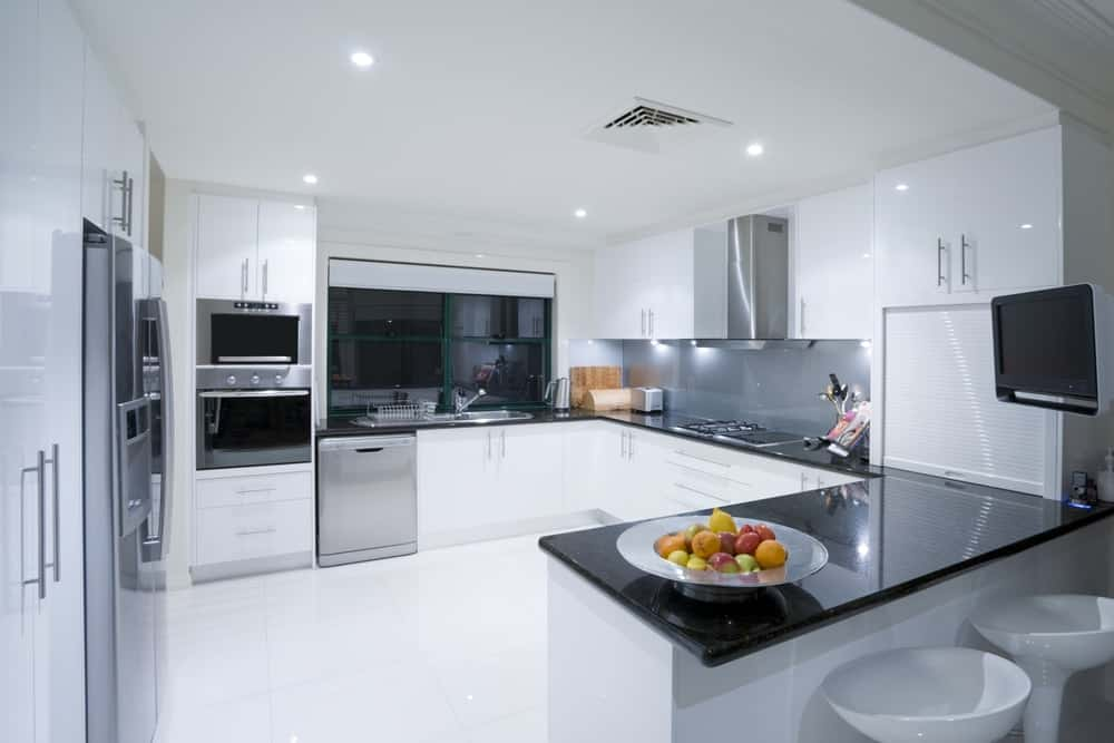 A bright kitchen that has a U-shaped peninsula that opens a large central floor space.