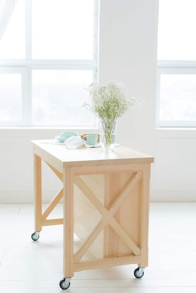 This is a charming mobile kitchen island made of light wood.