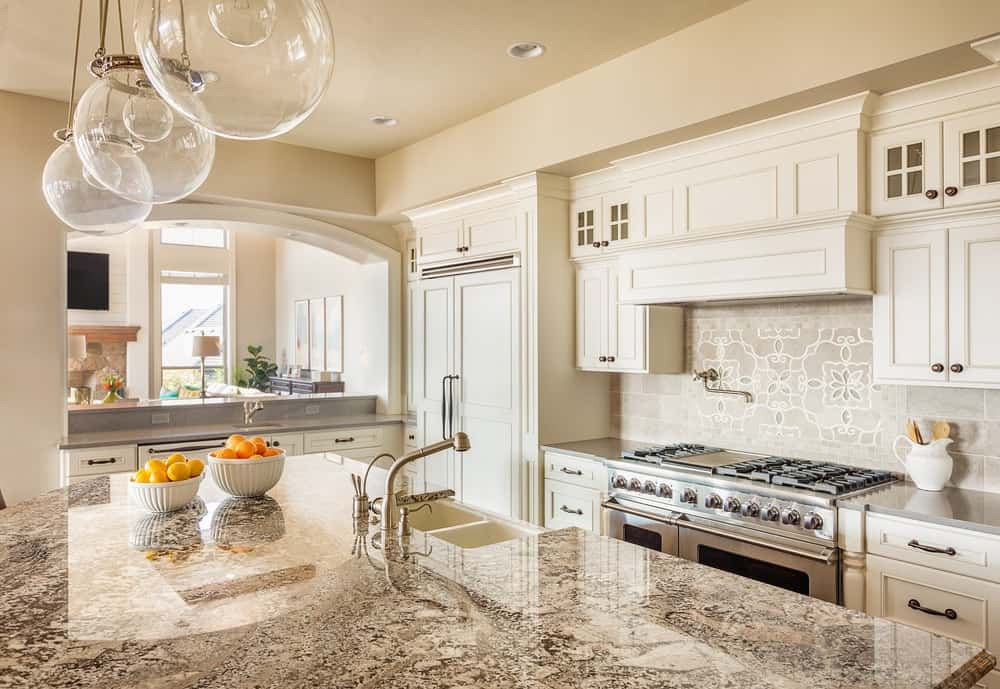 This gorgeous kitchen has a secondary sink at the kitchen island across from the cooking area.