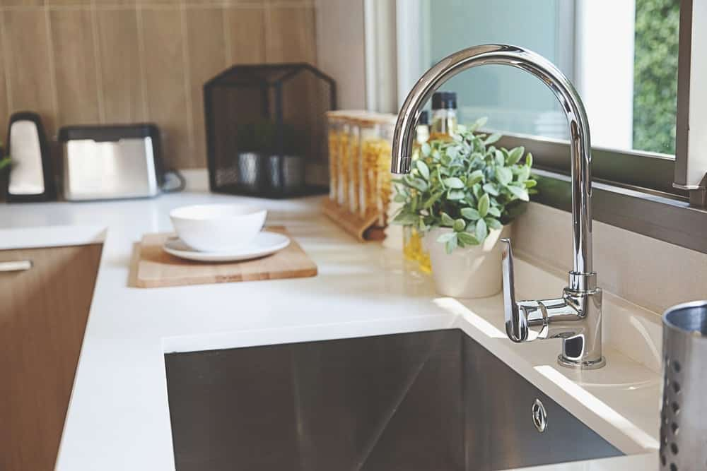 This kitchen's deep sink is paired with a stainless steel goose neck faucet.