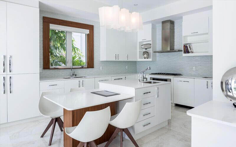 This white kitchen has a white center island with a built-in white tabletop paired with modern chairs and lit with stunning pendant lights.