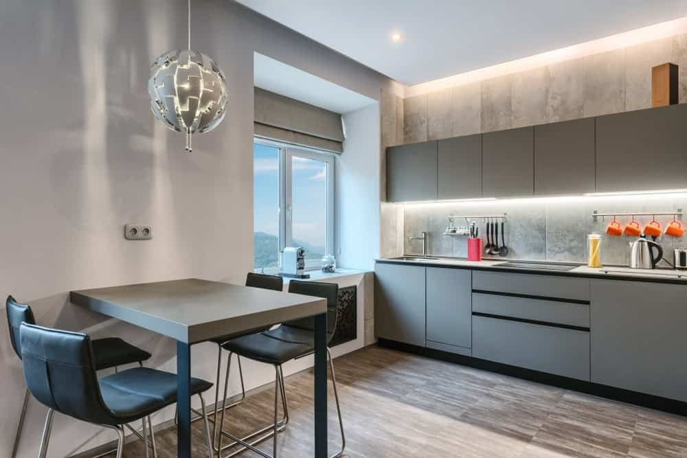 The modern kitchen with mounted built-in table over a stunning pendant light. It also has grey cabinets and drawers that match the flooring.