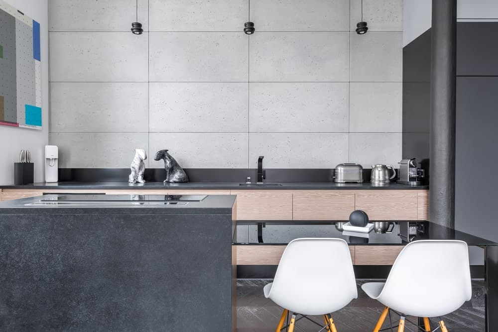 A small kitchen features a U-shaped island with a built-in metallic black table paired with two white chairs.