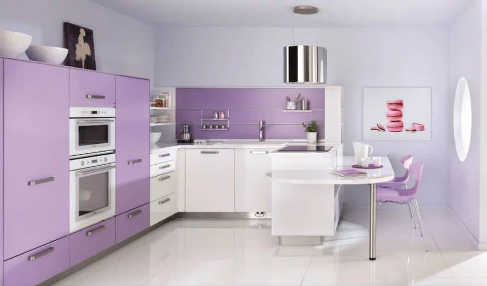 This kitchen features violet drawers and cabinets. It also has a built-in white table on the white tile flooring.