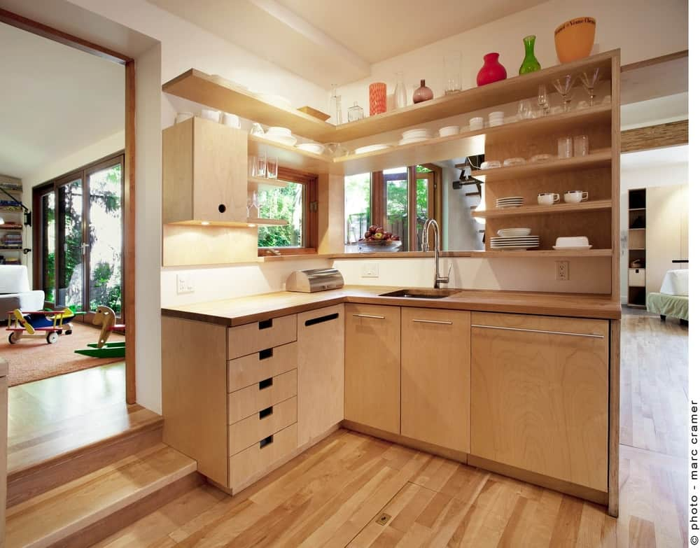 Mini L-shaped kitchen highlighting wooden floating shelves and cabinetry fixed on the white walls. It is fitted with a sink and chrome spigot.