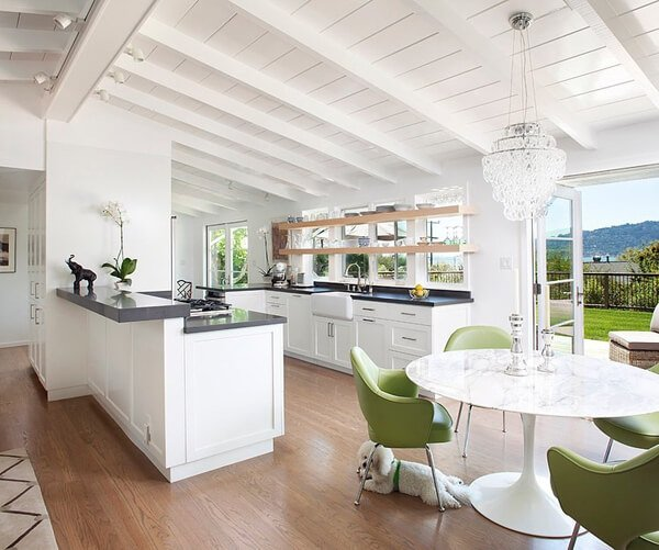 The vaulted ceiling and glass dividers make this room breezy and brilliant. Add to that the use of white, floating shelves, earthy colored, and light green, we get a fresh looking kitchen.