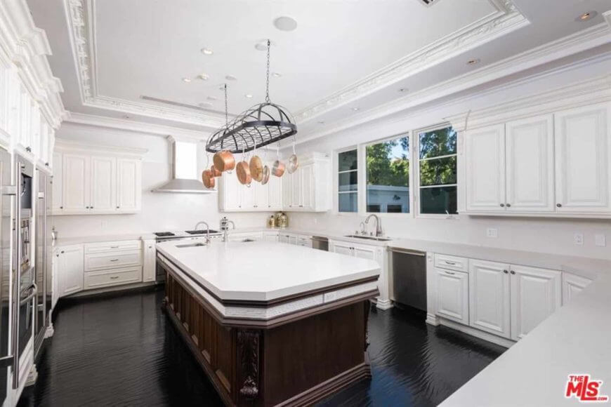 This kitchen features a white marble top kitchen island on the shiny black flooring. It also has white cabinets and drawers that match the walls and ceiling.