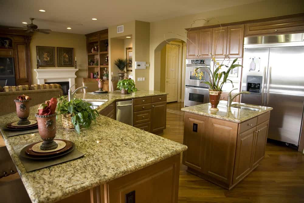 This kitchen features a gorgeous marble top countertops and wooden cabinets, and stainless steel appliances.