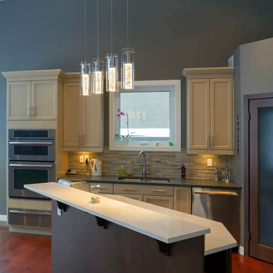 The kitchen with white marble top kitchen island lit by stunning pendant lights and huge wooden cabinets.