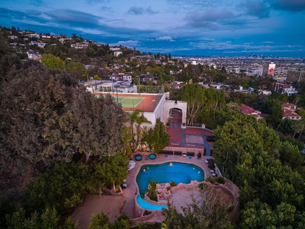 This aerial view focuses on the side of the home, featuring its swimming pool surrounded by landscaping trees. Images courtesy of Toptenrealestatedeals.com.