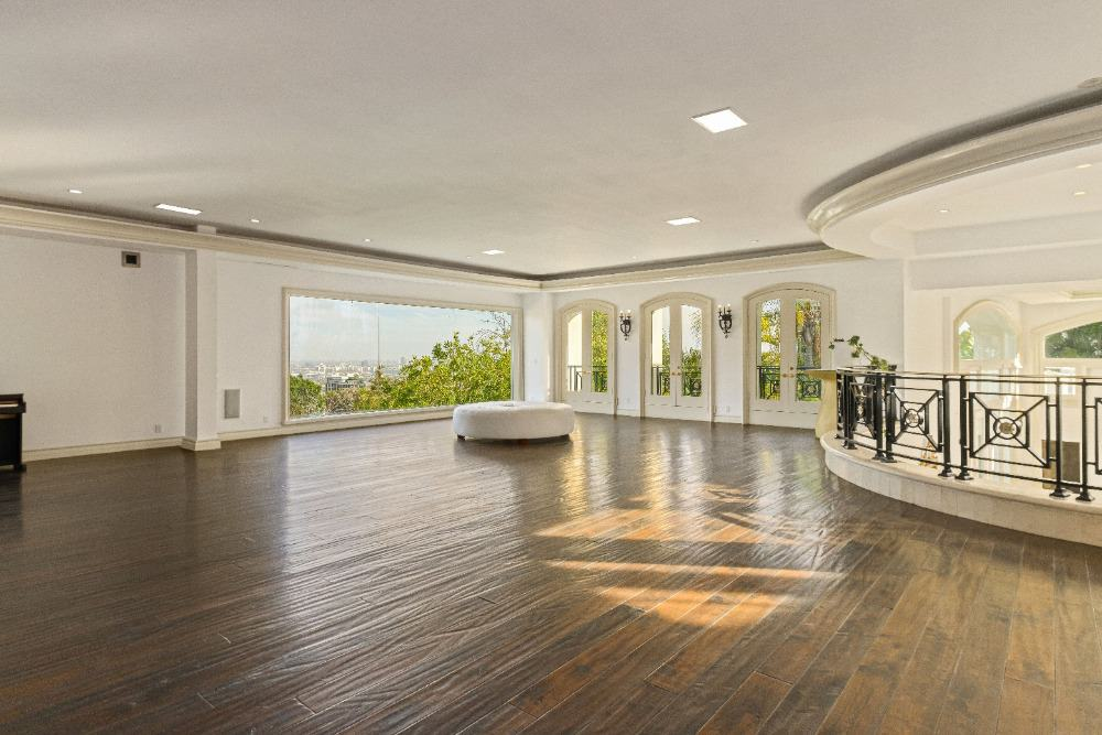 An empty second floor landing with white walls and hardwood floors, along with glass windows. Images courtesy of Toptenrealestatedeals.com.