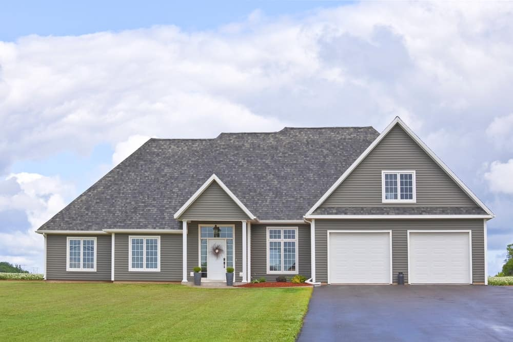 Family home with a dark vinyl siding, a double-car garage, and a covered front porch.